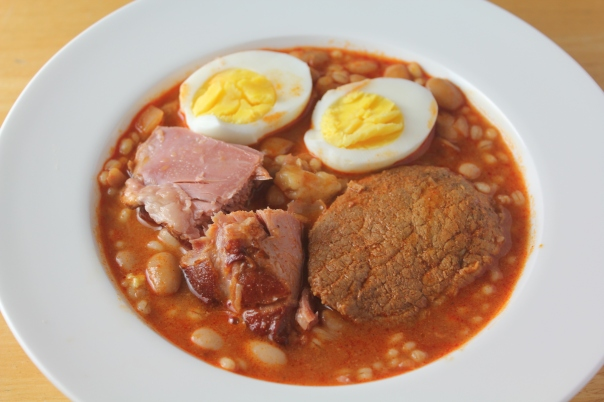 Bean stew topped with smoked duck breast, beef, and a halved egg.