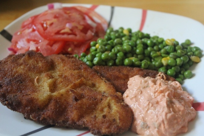 Fried breaded chicken served with peas, tomatoes, and Hungarian-style tzatziki.